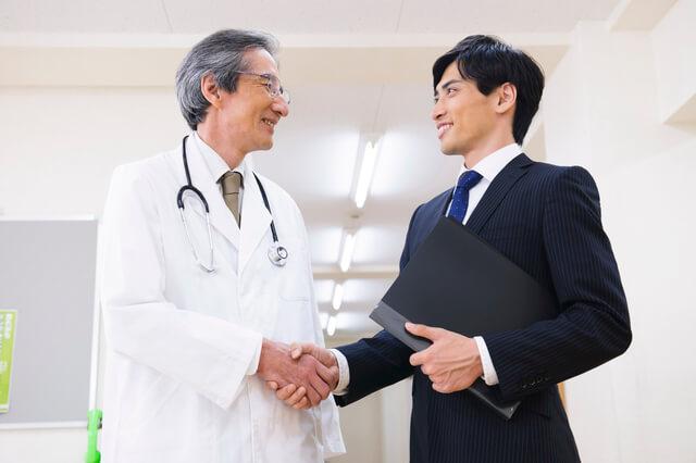 医師と握手するMR
