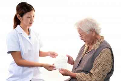 在宅ワークで高齢者に薬の説明をする薬剤師