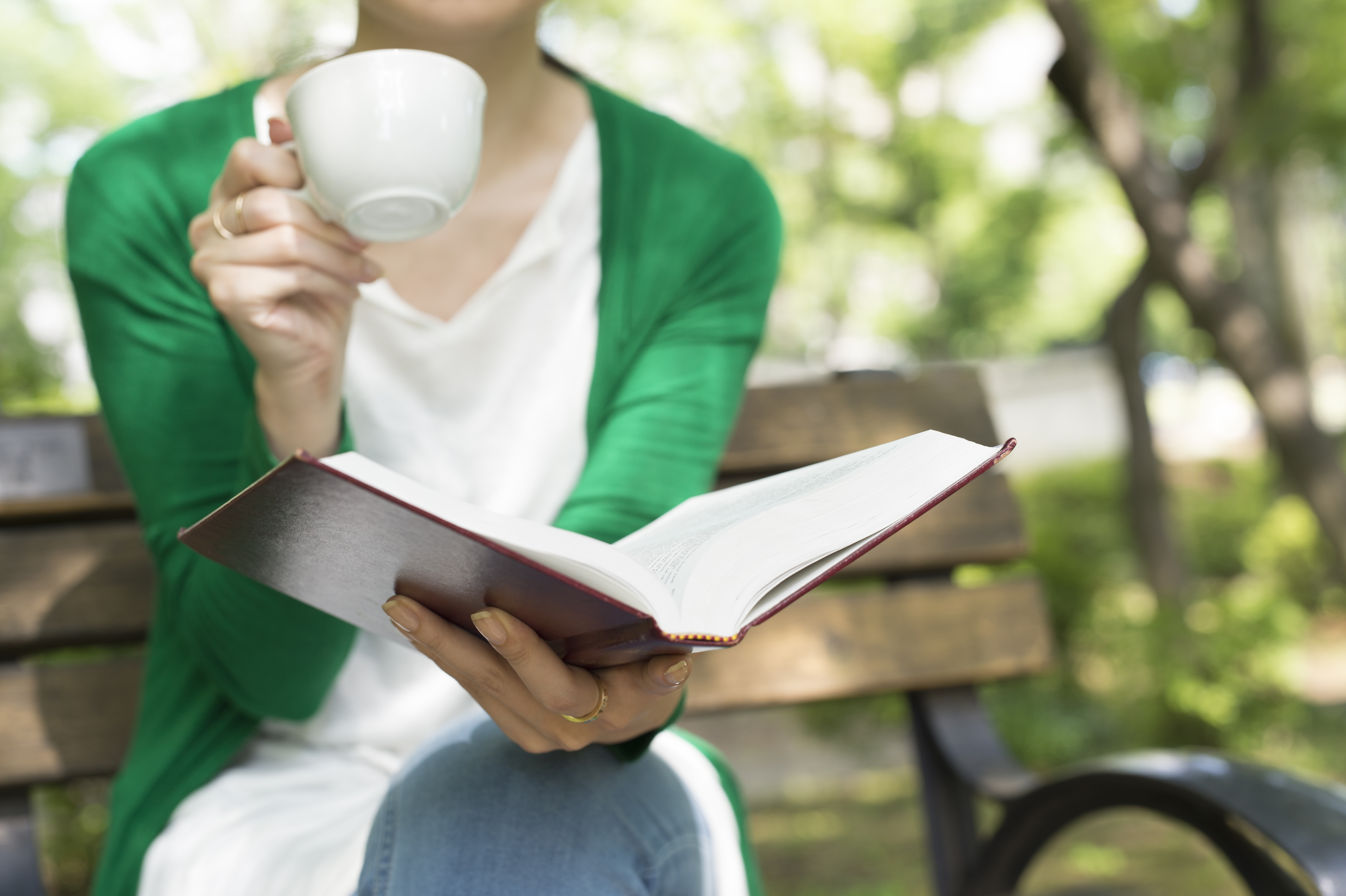 Women have a reading with a cup of coffee in the park