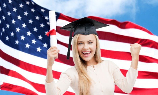 happy student girl with diploma over american flag
